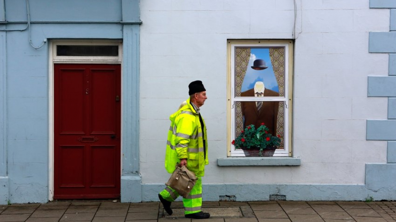 A man walks past an empty building, which has been covered with artwork to make it look more appealing, in the village of Bushmills on the Causeway Coast August 19, 2013. One of the homes of Irish whiskey has taken a scheme developed in Northern Ireland of erecting fake shop fronts where derelict buildings lie and has truly run with it in a bid to woo tourists. Bushmills, best known as the village where the whiskey of the same name was distilled for the first time 400 years ago, is now also becoming recognisable for the artwork and graphics that brighten up shop fronts left empty during the economic downturn. Picture taken August 19, 2013. REUTERS/Cathal McNaughton (NORTHERN IRELAND - Tags: BUSINESS SOCIETY TRAVEL) ATTENTION EDITORS: PICTURE 14 OF 20 FOR PACKAGE 'NORTHERN IRELAND'S TROMPE L'OEIL'SEARCH 'BUSHMILLS ART' FOR ALL IMAGES - RTX1315P